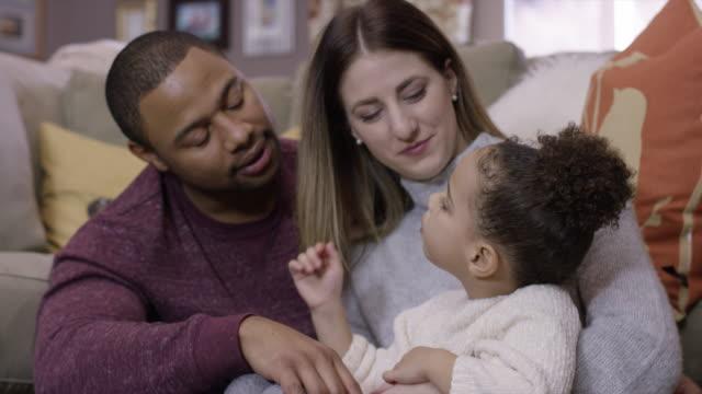 vídeos de stock, filmes e b-roll de família de raça mista, sentado no chão em sua casa - miscigenado
