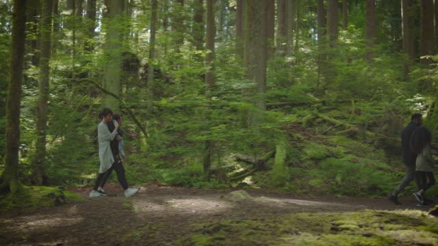 vídeos y material grabado en eventos de stock de mixed race family walk through the forest - acera