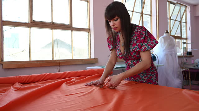 mixed race fashion designer cutting fabric on workbench - workbench stock videos & royalty-free footage