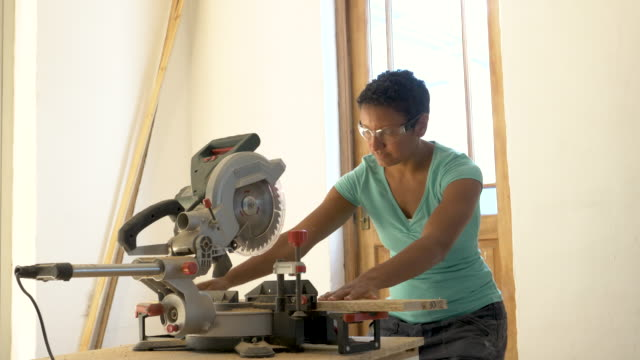 vídeos de stock, filmes e b-roll de mixed race female carpenter using electric saw - serra circular