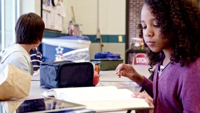 vídeos de stock e filmes b-roll de mixed race female middle school student studies while eating lunch - aluna da escola secundária