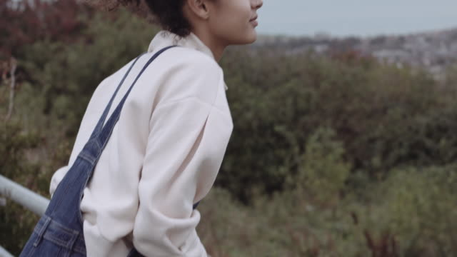 vidéos et rushes de mixed race female outdoors jumping on gate and looking at view, wearing sweater in autumn with moody sky - origine ethnique