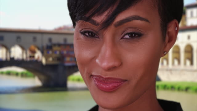 mixed race female traveling in florence smiling at camera near ponte vecchio - ponte stock videos & royalty-free footage