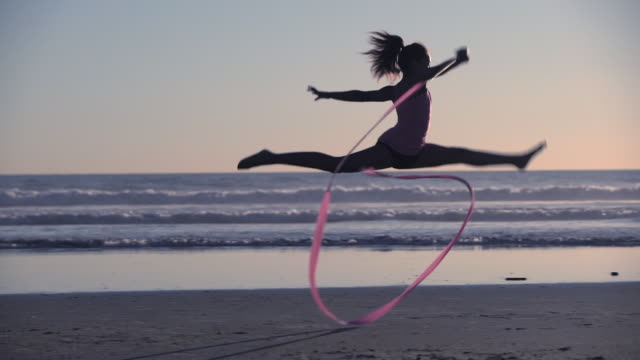 ws sm mixed race girl dancing with a ribbon on the beach at sunset - ballet dancing stock videos & royalty-free footage