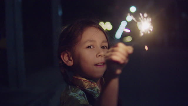 mixed race girl holding christmas sparkler in chinese new year - sparkler stock videos & royalty-free footage