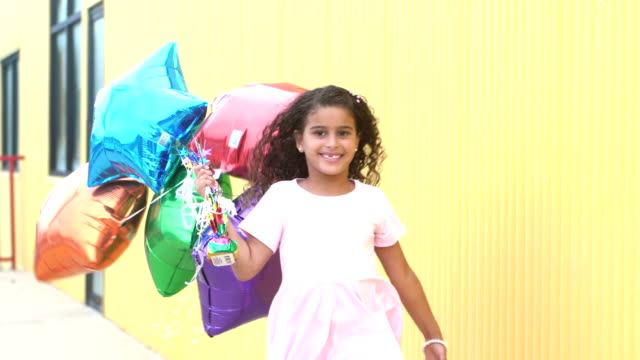 mixed race girl running by with bunch of balloons - moving toward stock videos & royalty-free footage