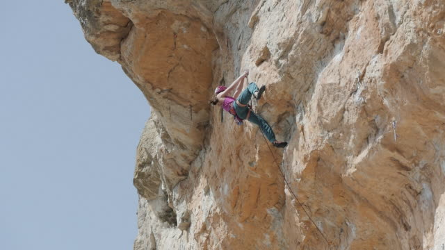 Mixed race girl slipping while climbing sheer cliff