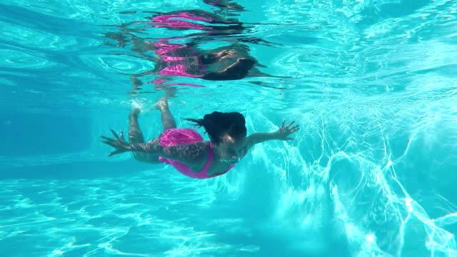 Mixed race girl swimming underwater