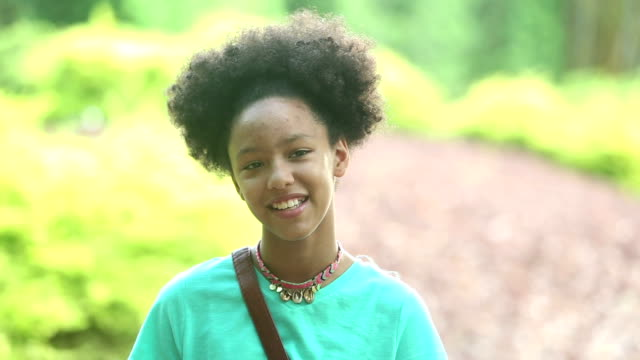 mixed race girl with afro at the park, looking at camera - pre adolescent child stock videos & royalty-free footage