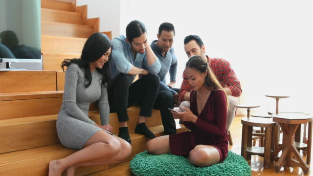 stockvideo's en b-roll-footage met gemengde ras groep vrienden kijken naar een mobiele telefoon - mixed race person
