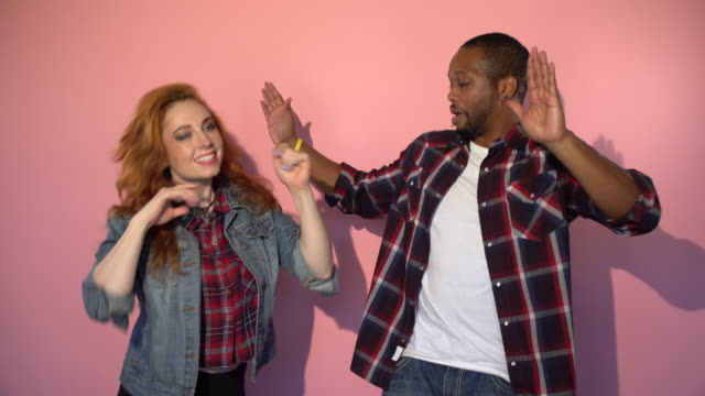vídeos de stock e filmes b-roll de mixed race hipster couple dancing in front of pink background - fundo colorido