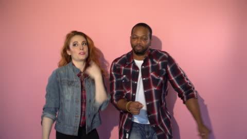 vidéos et rushes de race mixte hipster couple dansant devant fond rose - fond coloré