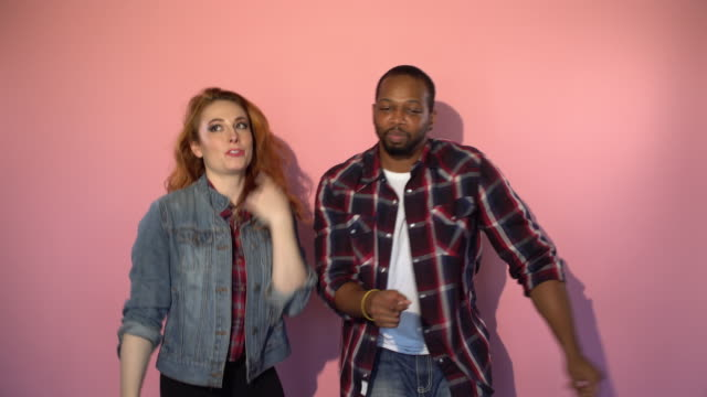mixed race hipster couple dancing in front of pink background - coloured background stock videos & royalty-free footage