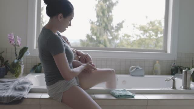 混血の幼児の女の子は彼女のお母さんからお風呂の準備をします - ユーラシアエスニシティ点の映像素材/bロール