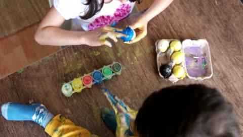 vídeos y material grabado en eventos de stock de raza mixta pequeña chica pintando huevos de pascua. - pascua