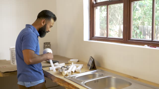 mixed race man doing diy renovation in a domestic house - bricolage video stock e b–roll