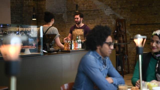 blandad ras man i café med väntar personalen arbetar i bakgrunden - servitris bildbanksvideor och videomaterial från bakom kulisserna