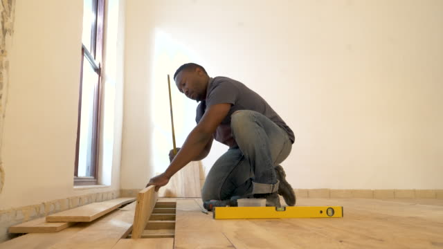 vídeos de stock e filmes b-roll de mixed race man laying wood floor in domestic house - só homens jovens