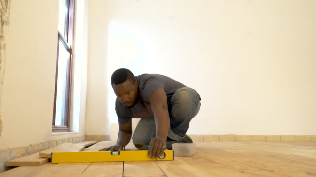 vidéos et rushes de mixed race man laying wood floor in domestic house - one young man only