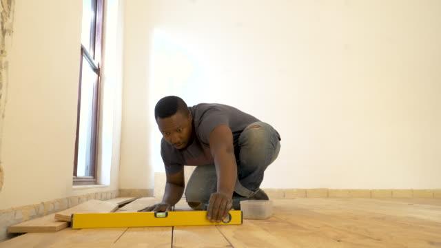 mixed race man laying wood floor in domestic house - 若い男性一人点の映像素材/bロール