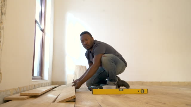 vídeos y material grabado en eventos de stock de mixed race man laying wood floor in domestic house - carpintería