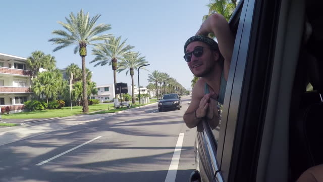 Mixed race man leaning out car window in tropical city