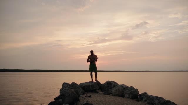 vídeos de stock, filmes e b-roll de mixed race man playing ukulele on rocks near water at sunset - ukulele