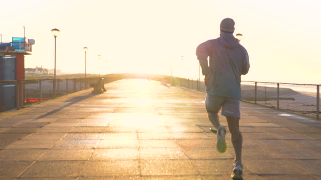 mixed race man running along a boardwalk by a beach at sunrise - weekend activities stock videos & royalty-free footage