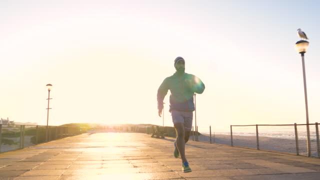 stockvideo's en b-roll-footage met mixed race man running along a boardwalk by a beach at sunrise - mixed race person