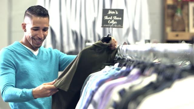 vídeos y material grabado en eventos de stock de hombre de raza mixta que compras en tienda de ropa - ropa de caballero