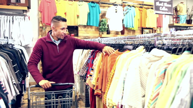 Mixed race man shopping in clothing store