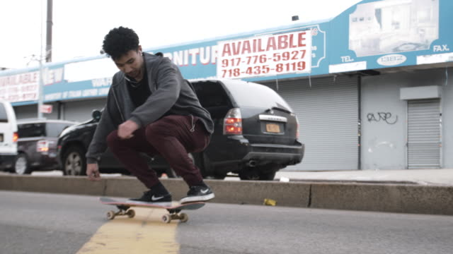 mixed race man skateboarding in the streets of brooklyn - hipster culture stock videos & royalty-free footage