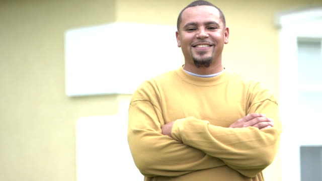 Mixed race man smiling at camera, arms crossed