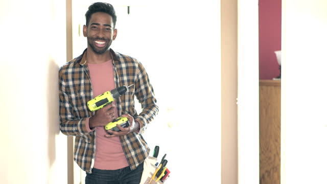 mixed race man standing inside home with drill and tools - tool belt stock videos and b-roll footage