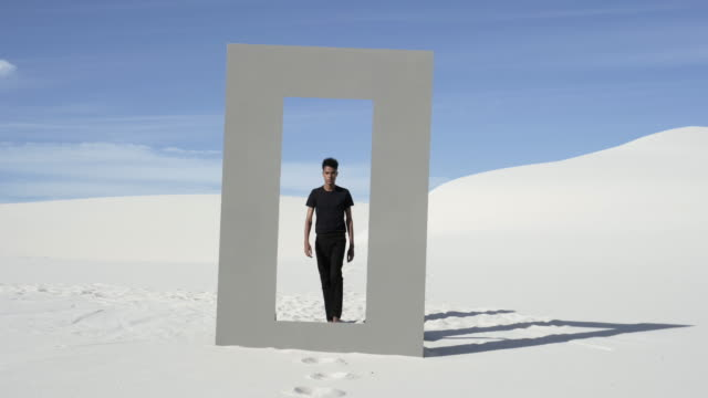 vídeos de stock, filmes e b-roll de mixed race man walks through doorframe in desert, wide - branco