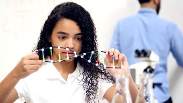 lo studente della scuola media di razza mista prende appunti mentre esamina il modello di elica del dna - modello dimostrativo video stock e b–roll