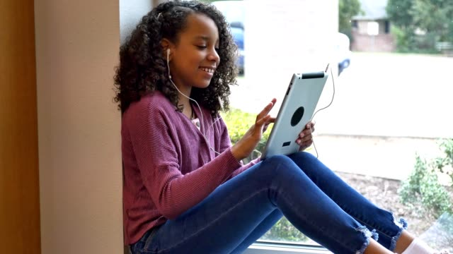 mixed race middle schoolgirl uses digital tablet at school - junior high stock videos & royalty-free footage