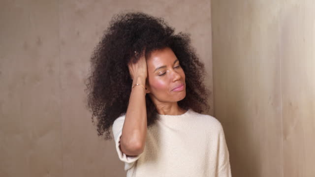 vídeos y material grabado en eventos de stock de mixed race middle-age woman runs hands through natural hair as she looks at camera, against a wooden wall background. - sobreexpuesto