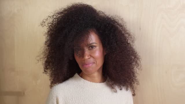 mixed race middle-age woman with natural hair laughs and shakes head at camera, against a wooden wall background. - natural hair stock videos & royalty-free footage