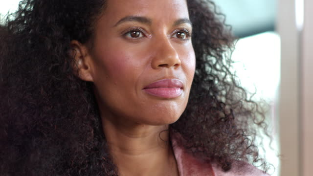 mixed race, middle-aged woman with natural hair looks up, then turns toward camera and brings hand up to face, against blurred background. - mature women stock videos & royalty-free footage