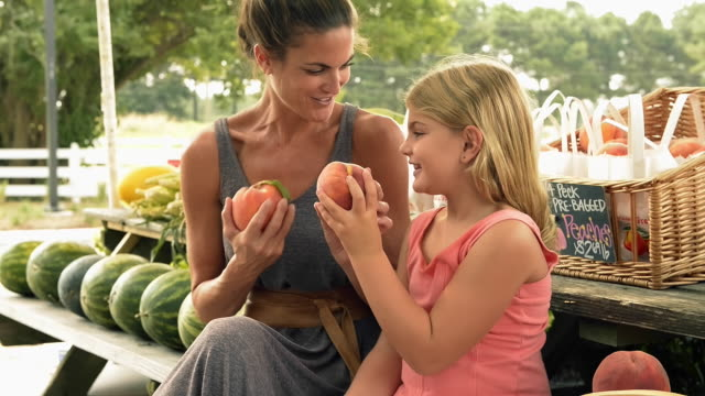 Mixed race mother and daughter smelling peaches at farm stand
