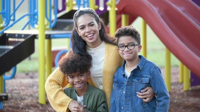 vídeos de stock, filmes e b-roll de mãe e filhos mestiços no playground - família de dois filhos