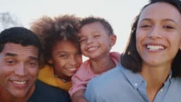 Mixed race parents piggybacking their kids in the garden, looking to camera and laughing, close up