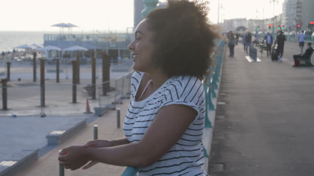 mixed race person looks out over beach standing on promenade. - brighton england stock videos & royalty-free footage