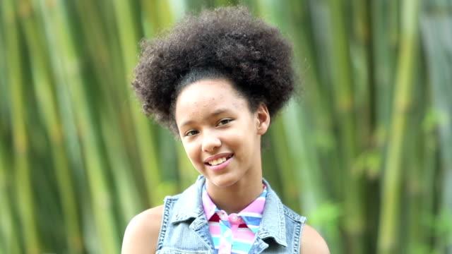 gemischte rassen pre-teen mädchen mit afro lächelnd in die kamera - 12 13 years stock-videos und b-roll-filmmaterial