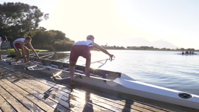 stockvideo's en b-roll-footage met mixed race rowing team preparing to go training - watersport