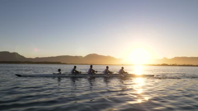 vídeos de stock, filmes e b-roll de mixed race rowing team training on a lake at dawn - remo parte de navio