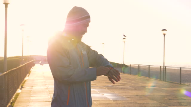 stockvideo's en b-roll-footage met mixed race runner resting on a boardwalk by a beach at sunrise - mixed race person