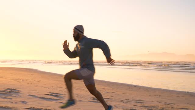mixed race runner sprinting on a beach at sunrise - トラック競技点の映像素材/bロール