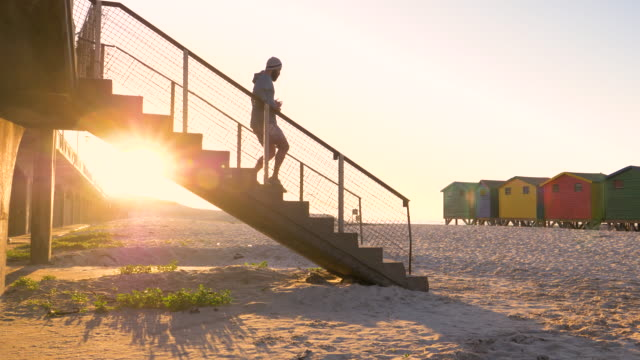 mixed race runner training on a beach at sunrise - steps stock videos & royalty-free footage